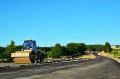 Асфальтируя строительства с коммерчески оборудованием ремонта Ролики дороги выравнивая свежую мостовую асфальта стоковое изображение rf