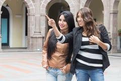 2 латинских девушки усмехаясь и указывая место Стоковая Фотография