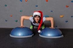 Атлетическая девушка в красной шляпе эльфа, делает нажим-вверх от шариков для баланса и улыбок стоковое фото rf