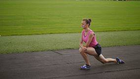 Атлетическая девушка делая выпады limbering вверх на стадионе сток-видео