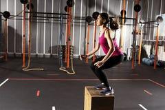 Атлетическая девушка кладет тренировки в коробку скачки на спортзале Стоковая Фотография RF