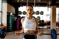 Атлетическая девушка одетая в белых верхней части и колготках спорт поднимает штангу в спортзале стоковое изображение