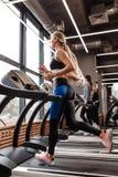 Атлетическая девушка с длинными светлыми волосами одетыми в sportswear бежит на третбане перед окнами внутри стоковые изображения rf