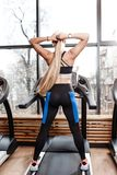 Атлетическая девушка с длинными светлыми волосами одетыми в sportswear стоит на третбане перед окнами внутри стоковая фотография
