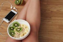 Атлетическая девушка с здоровой едой на ее ногах Стоковые Фотографии RF