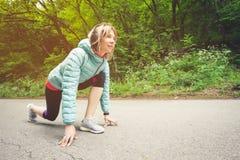 Атлетическая женщина бежать в дороге сельской местности Бегун фитнеса женский в готовой линии представлении старта outdoors в спр стоковое изображение