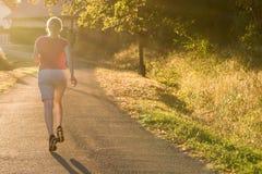 Атлетическая женщина бежать на следе сельской местности в свете восхода солнца стоковая фотография rf