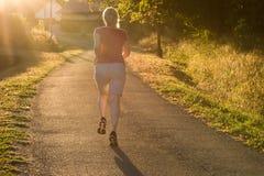 Атлетическая женщина бежать на следе сельской местности в свете восхода солнца стоковое фото