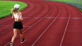 Атлетическая женщина бежит на идущем следе Девушка спорта jogging через стадион сток-видео