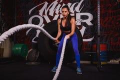 Атлетическая женщина делая некоторое crossfit работает с тяжелой веревочкой стоковые фото