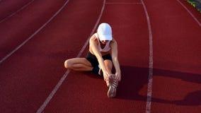 Атлетическая женщина протягивая ноги перед бегом на идущем следе видеоматериал