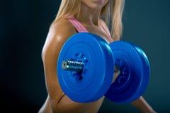 Атлетическая молодая женщина делая разминку фитнеса с гантелями на темной предпосылке студии Стоковое Изображение