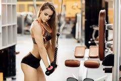 Атлетическая молодая женщина делая тренировку на трицепсе в кроссовере в спортзале стоковые фото