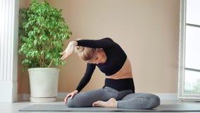 Атлетическая молодая женщина показывая тонкое гибкое тело сидя на съемке циновки дома полной акции видеоматериалы