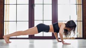 атлетическая спортсменка, молодая кудряшка, показывающая упражнения на мате в гимнастической студии акции видеоматериалы