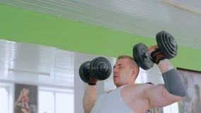Атлетические гантели молодого человека поднимаясь на спортзале акции видеоматериалы