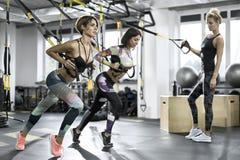 Атлетические девушки тренируя в спортзале Стоковая Фотография