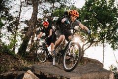 атлетические молодые пробные велосипедисты ехать на утесах стоковые фотографии rf