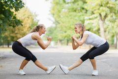 Атлетические, привлекательные, подходящие девушки разрабатывая совместно на предпосылке парка Концепция гимнастики Стоковая Фотография