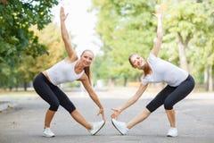 Атлетические, привлекательные, подходящие девушки разрабатывая совместно на предпосылке парка Концепция гимнастики Стоковое Изображение RF