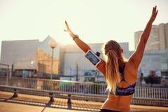 Атлетический бегун девушки поднял ее оружия вверх стоя на brid Стоковые Фотографии RF