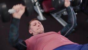 Атлетический и привлекательный человек делая жим лежа гантели в спортзале сток-видео
