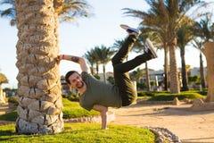 Атлетический молодой красивый человек, делающ handstand на летнем отпуске, ослабляя в курорте гостиницы пляжа с ладонями, b-мальч Стоковое Фото