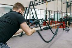 Атлетический мышечный бородатый человек работая в спортзале с веревочками сражения Спорт, тренировка, люди, здоровая концепция об стоковое фото
