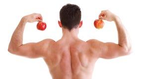 Атлетический сексуальный строитель мыжского тела держа красное яблоко Стоковые Фотографии RF