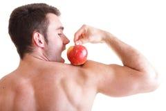Атлетический сексуальный строитель мыжского тела держа красное яблоко Стоковое фото RF