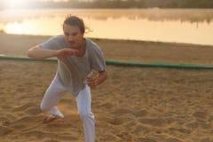 Атлетический совершитель capoeira делая движения на пляже Стоковые Фото