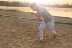 Атлетический совершитель capoeira делая движения на пляже Стоковые Изображения