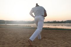 Атлетический совершитель capoeira делая движения на пляже Стоковые Изображения RF