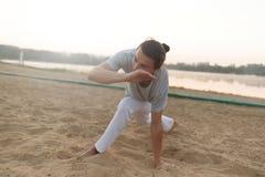 Атлетический совершитель capoeira делая движения на пляже Стоковые Фотографии RF