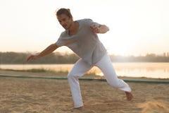 Атлетический совершитель capoeira делая движения на пляже Стоковая Фотография