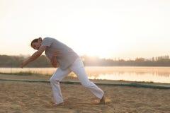 Атлетический совершитель capoeira делая движения на пляже Стоковое Фото