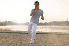 Атлетический совершитель capoeira делая движения на пляже Стоковое Изображение RF