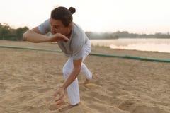 Атлетический совершитель capoeira делая движения на пляже Стоковая Фотография RF