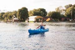 Атлетический спортсмен держа затворы пока сплавляющся на каяке на реке стоковые изображения