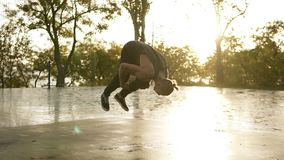 Атлетический человек в черных случайных одеждах выполняя сальто и прыжок кувырком акробатики на открытом воздухе - замедление ste акции видеоматериалы