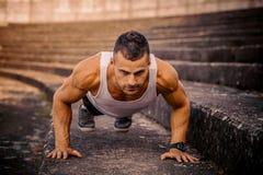 Атлетический человек делать нажимает поднимает стоковые фотографии rf