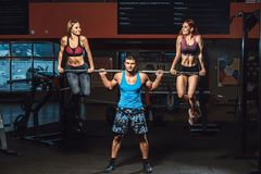Атлетический человек поднимает штангу при 2 девушки как вес и девушки вися от штанги штанга с 2 девушками на ей Стоковое Изображение