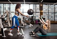 2 атлетических девушки одетой в sportswear делают тренировки для прессы на циновке для фитнеса с шариком фитнеса внутри стоковые изображения