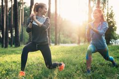 2 атлетических женских друз нося комбинезоны делая выпады совместно тренируя outdoors Стоковое фото RF