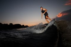 Атлетическое wakesurfer скача на ехать вниз с реки развевает Стоковые Фотографии RF