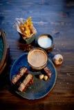 Атмосфера старого кафа Игрок с диском, стекло темного пива, хлеб чеснока и фраи Быстро-приготовленное питание Стоковое Изображение RF