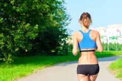 Атлетическая девушка в верхней части и шортах бежать на дороге в парке стоковое фото rf