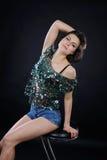 Атлетическая девушка в сияющих блузке и джинсовой ткани замыкает накоротко в студии Стоковые Фотографии RF
