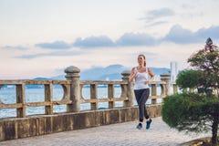 Атлетическая девушка на набережной Молодая спортсменка делая тренировки против моря стоковое изображение rf