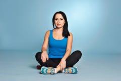 Атлетическая девушка при тело мышцы сидя на поле Стоковая Фотография RF